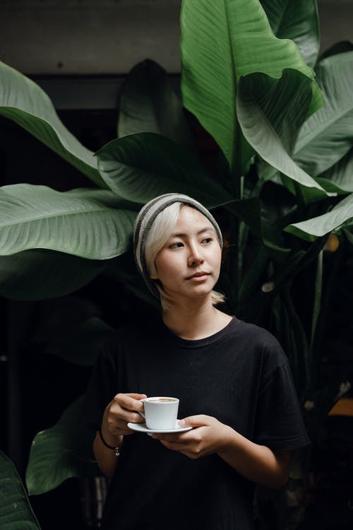 Slim Asian woman with coffee near big green potted plant