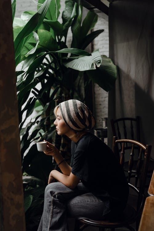 Side view of slim Asian female in gray jeans and striped beanie sitting on elegant chair and looking thoughtfully out of window while having quiet cup of coffee