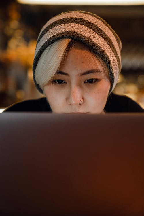 Young Asian female student in striped beanie hat sitting at table in cafe and browsing Internet on laptop while working on project