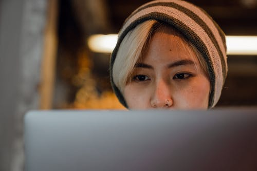 Young Asian female freelancer working on project on laptop