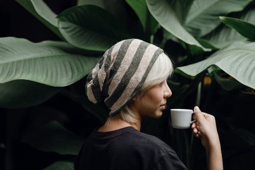 Calm woman in casual modern outfit enjoying cup of coffee