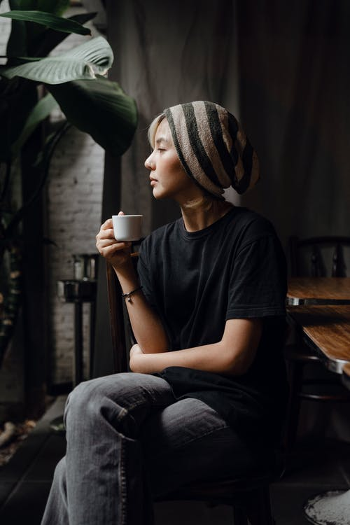 Slender Asian female having cup of coffee in quiet cafe