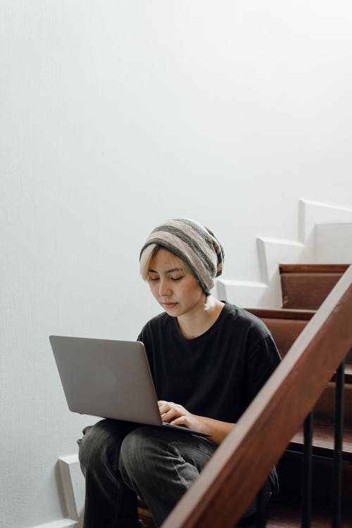 Young female working on laptop sitting on steps