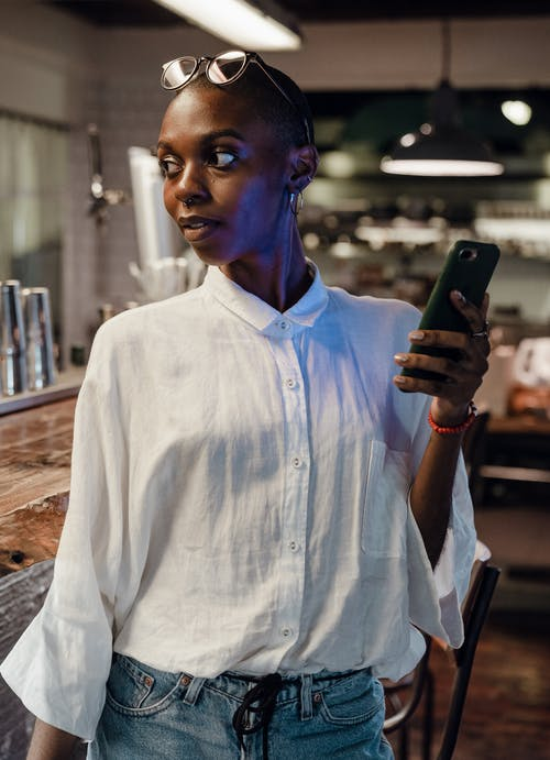 Trendy black woman with cellphone in cafe