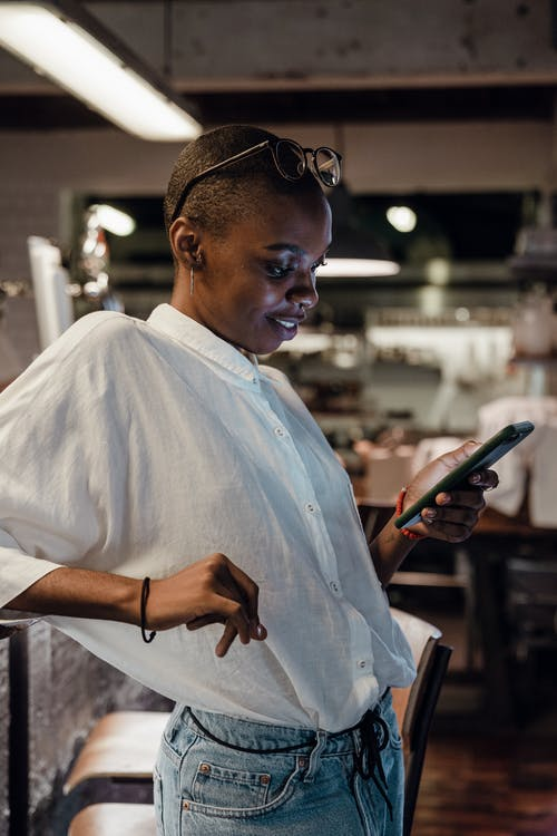 Content black female using smartphone in bar