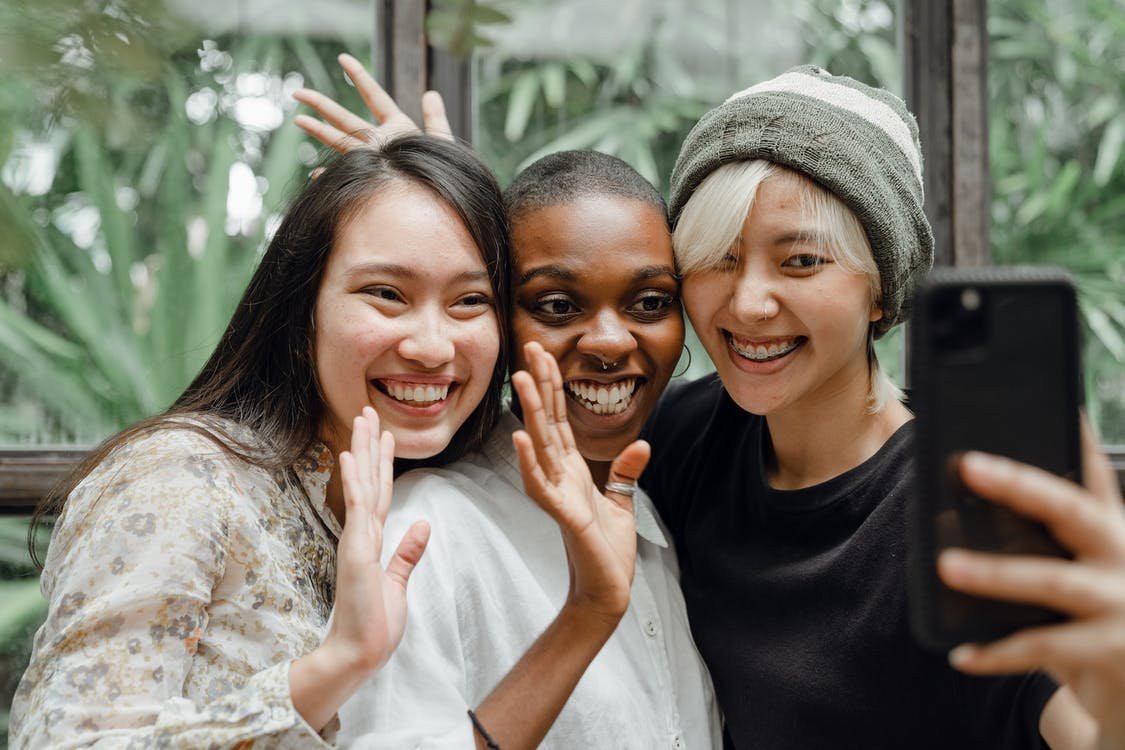 Cheerful Asian and African American young ladies waving hands and smiling at phone camera while taking selfie