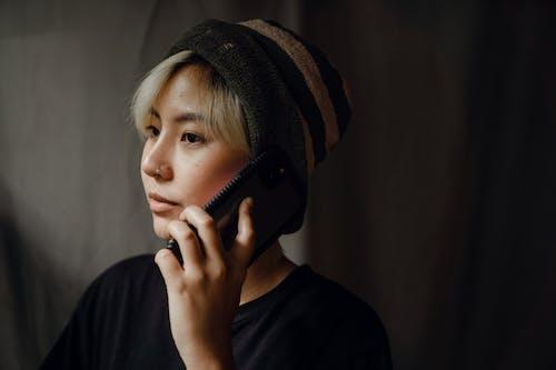 Serious female making call on mobile near dark studio background