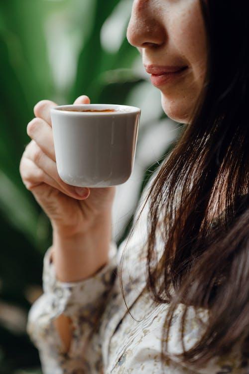 Crop woman tasting fresh coffee in cafe
