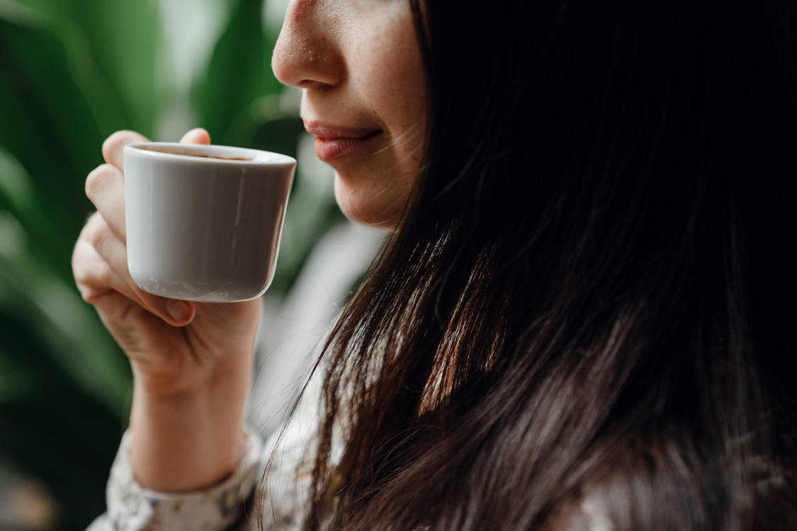 Crop female enjoying fresh aromatic coffee from little cup