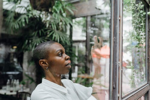 Through glass shot of serious slim African American woman in white shirt with ear hoops using mobile phone to take photo of street while standing near window in modern cafe