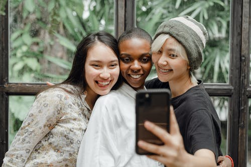 Cheerful young ladies hugging and taking selfie in modern cafe