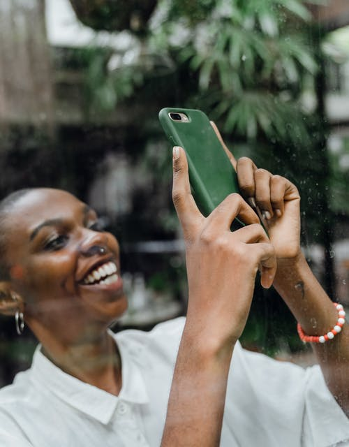 Happy young black woman taking photo of street through glass