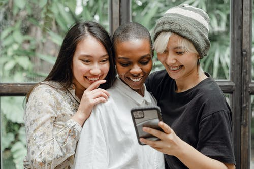 Happy young diverse female friends taking selfie on mobile phone