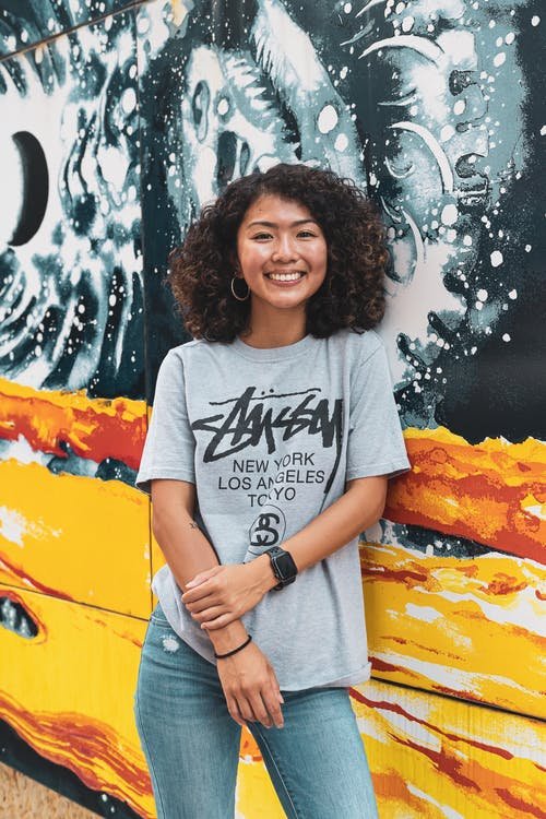 Woman in Gray and Black Crew Neck T-shirt Standing Beside Wall With Graffiti