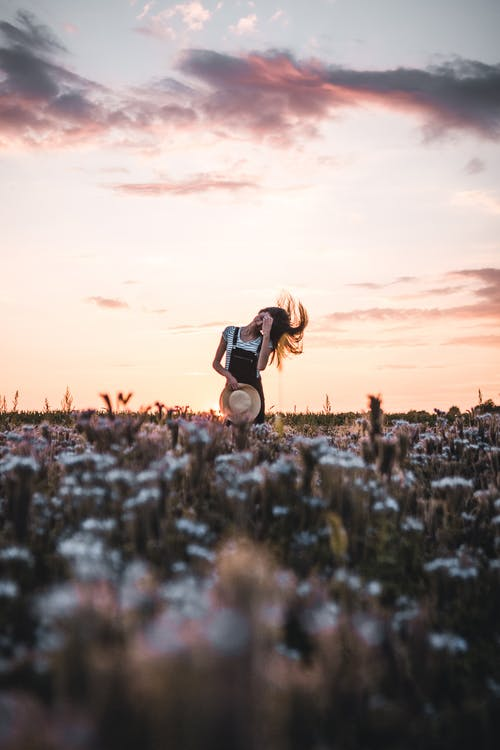 Woman in Black and White Dress on Brown Grass Field during Sunset