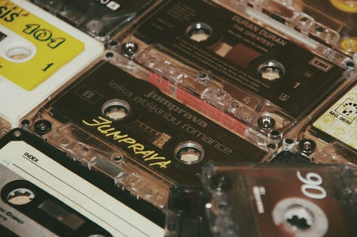 From above of different aged audio cassettes with inscriptions on plastic surface in flat