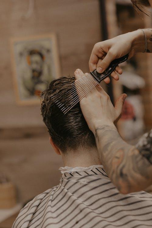 Man in Gray and White Stripe Long Sleeve Shirt Holding Hair Brush