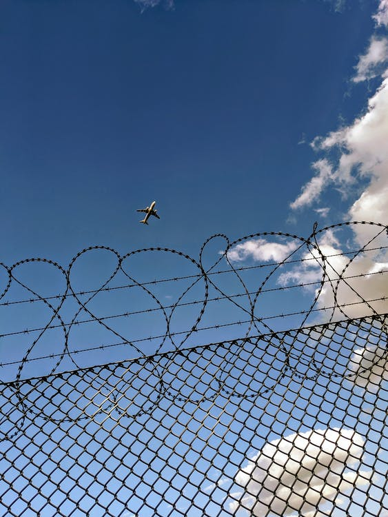 Flying airplane in blue sky above fence