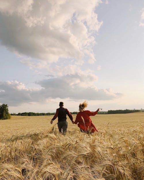 2 Women Walking on Brown Grass Field Under White Clouds