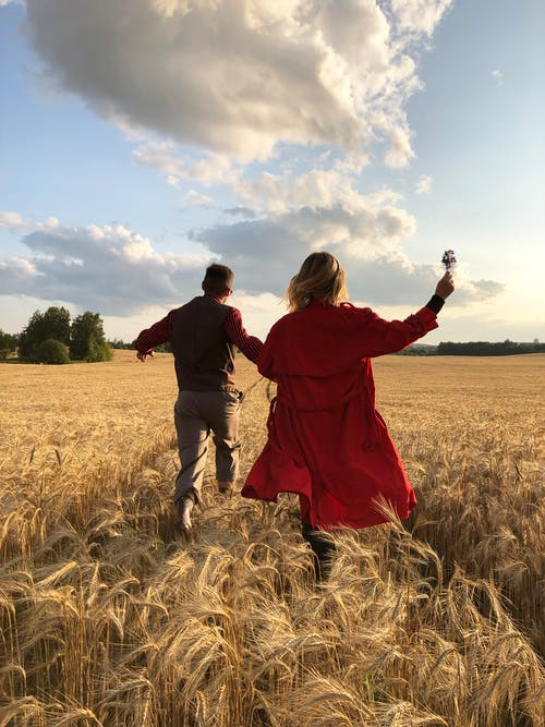 Man and Woman Holding Hands and Running on a Field