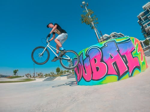 From below of young fit cyclist on bike practicing dirt jumping near bright platform with graffiti on city street