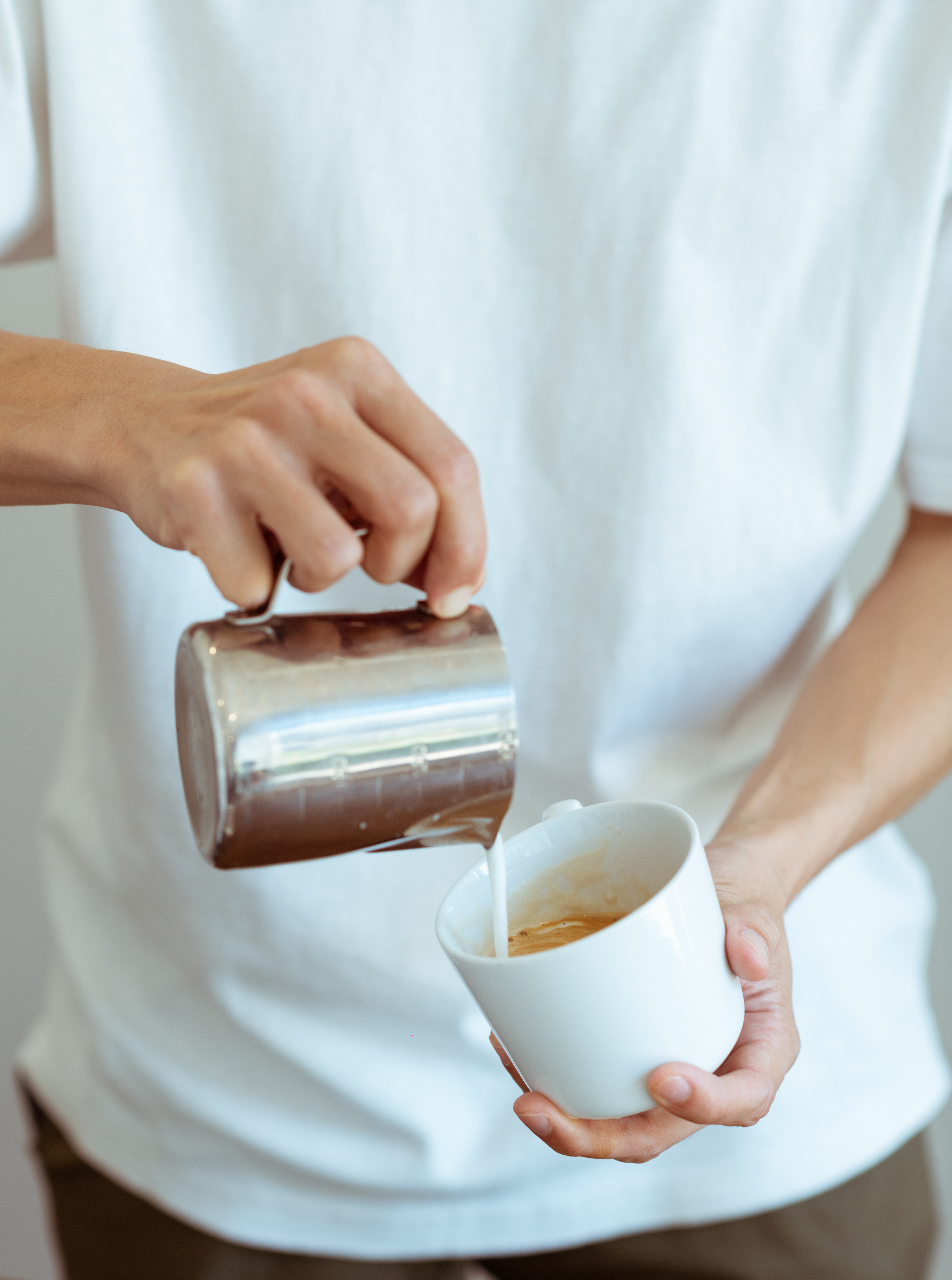 crop barista pouring whipped milk in white coffee cup