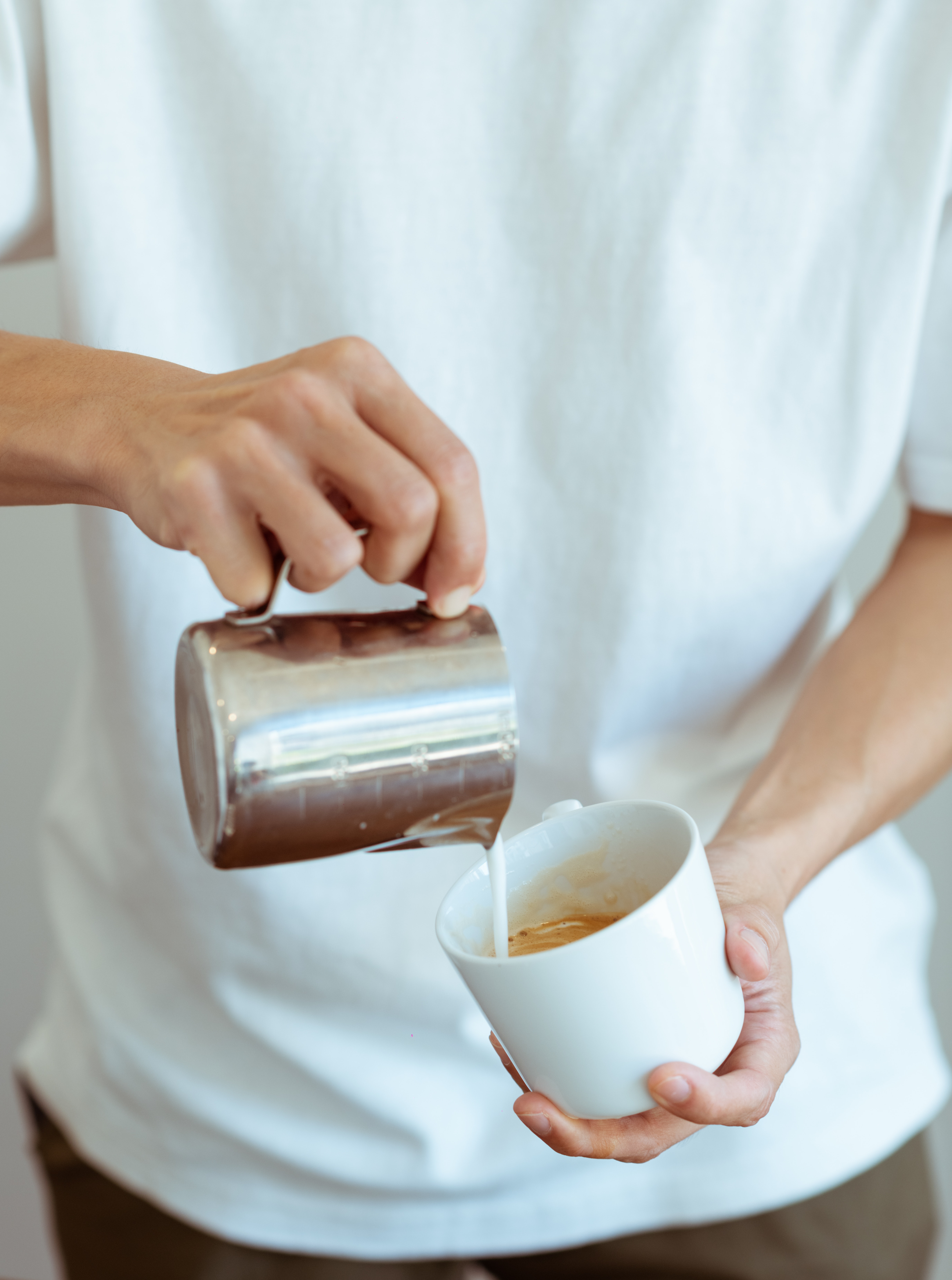 Crop barista pouring whipped milk in white coffee cup ...