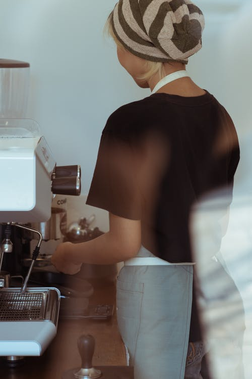 Through glass back view of anonymous female coffee house employee in black T shirt and slouchy knit beanie making fresh coffee using coffee machine