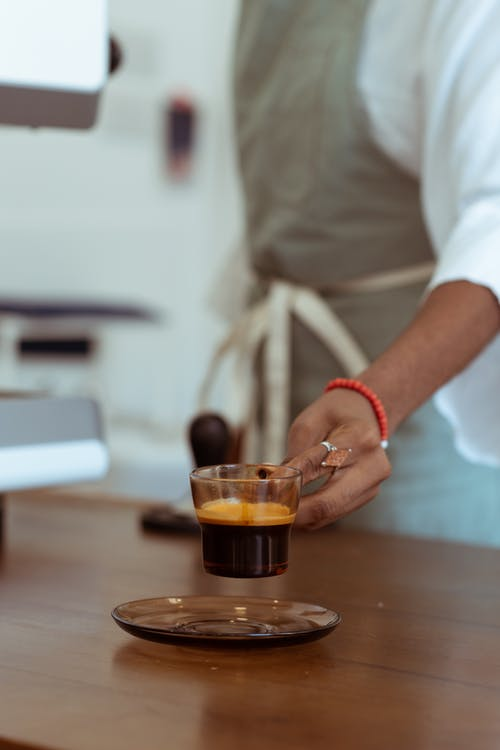 Crop barista placing cup of espresso on saucer for client