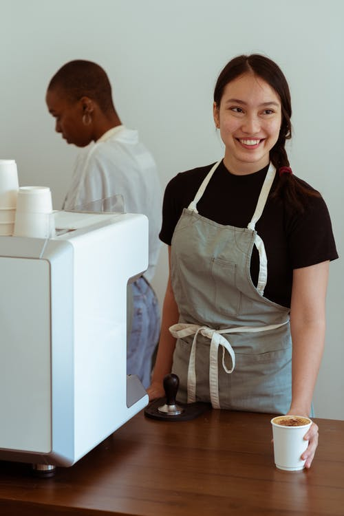 Cheerful female barista serving coffee to client