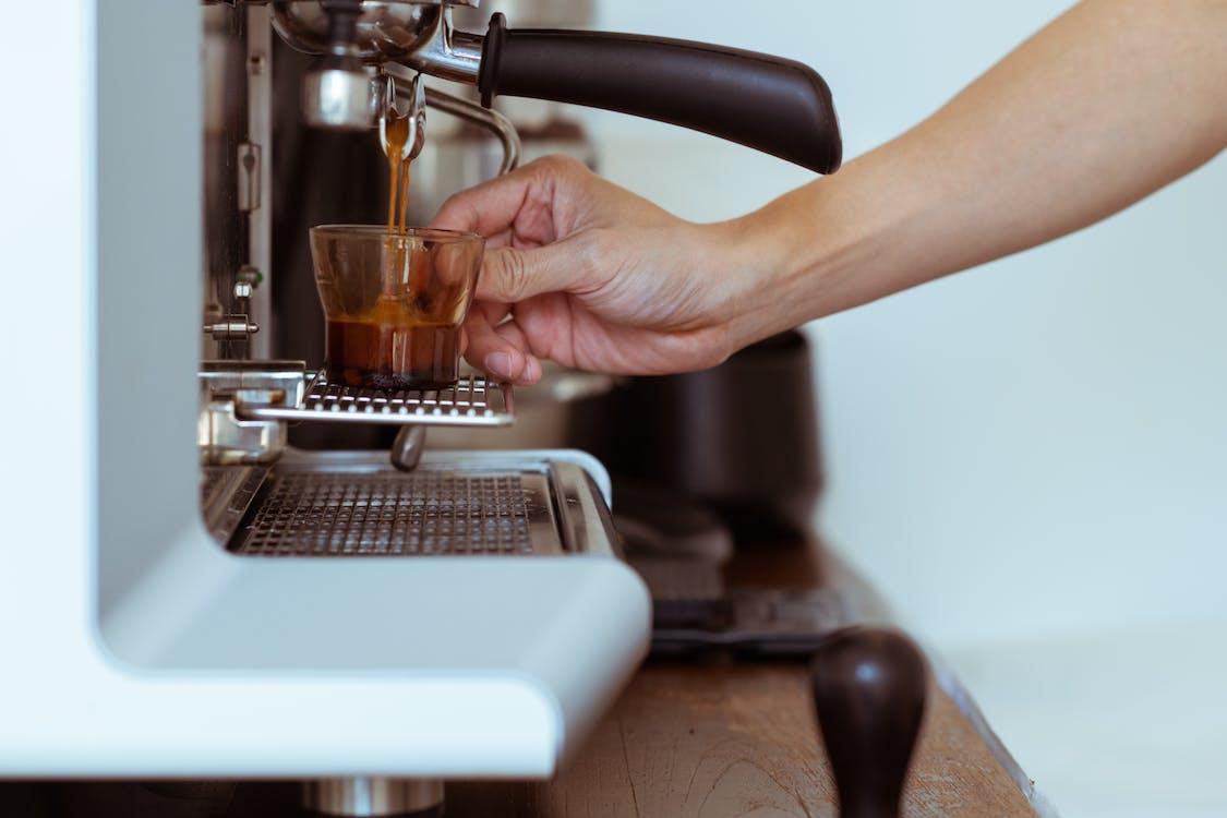 Crop barista making coffee in coffeemaker