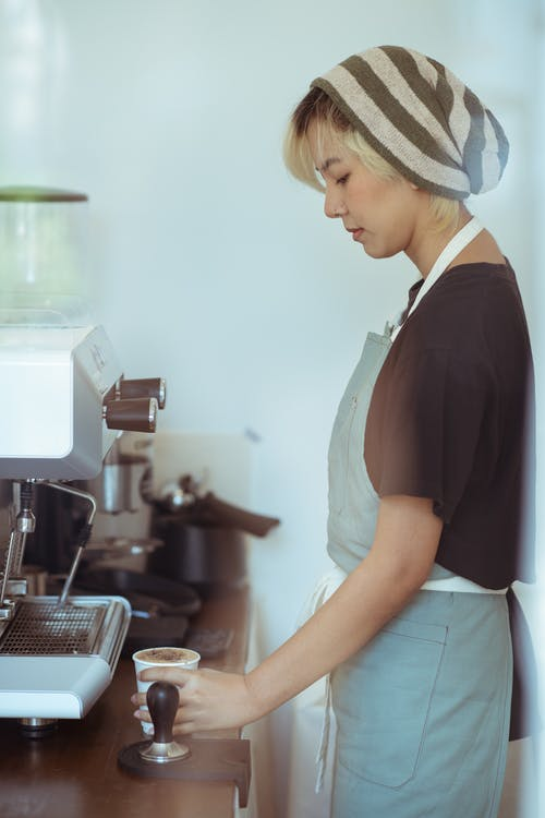 Through glass side view of serious young Asian female barista in apron preparing fresh coffee on ordinary workday at cafe
