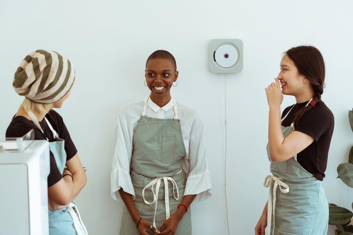 Positive young diverse female baristas in apron uniforms communicating with shy newcomer during break at work