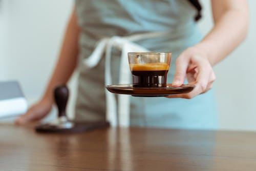 Crop barista with fresh black coffee ready for customer