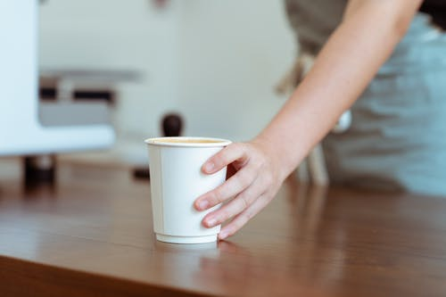 Crop barista serving coffee in paper cup