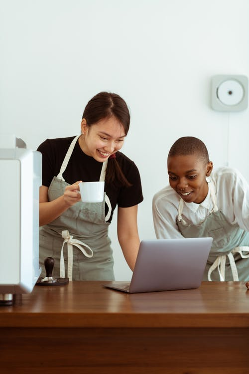 Cheerful colleagues in aprons working on laptop in kitchen
