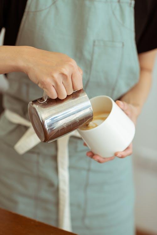 Crop barista preparing cappuccino and pouring milk into cup