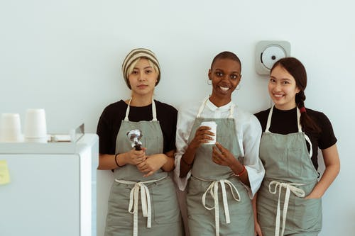 Happy waitresses with portafilter against white wall