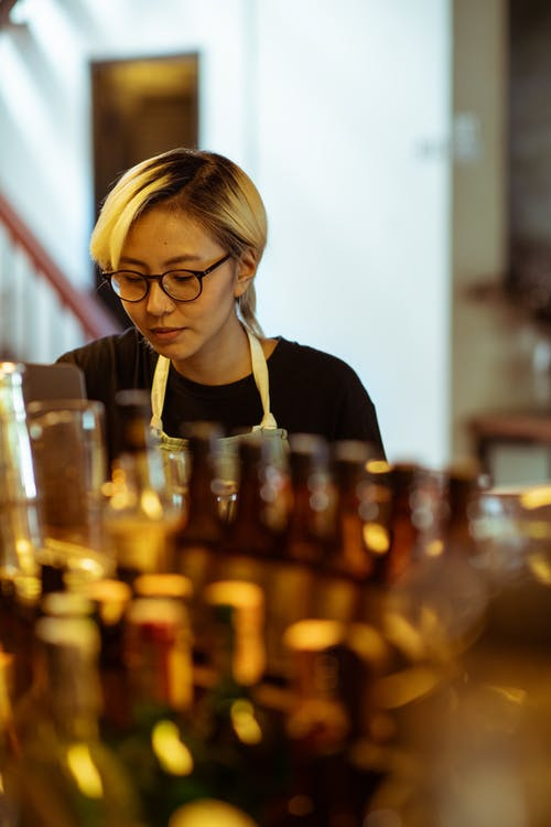 Content woman in black shirt behind row of bottles
