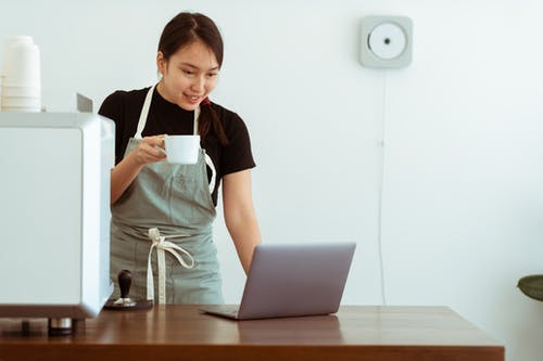 Cheerful woman with cup of beverage working on laptop