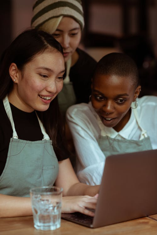 Smiling coworkers in aprons using laptop together