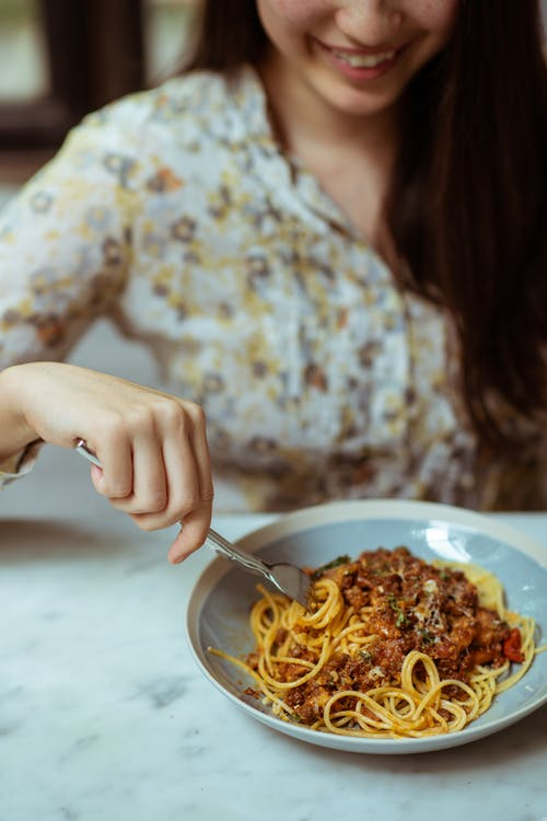 Crop cheerful woman eating pasta in cafe