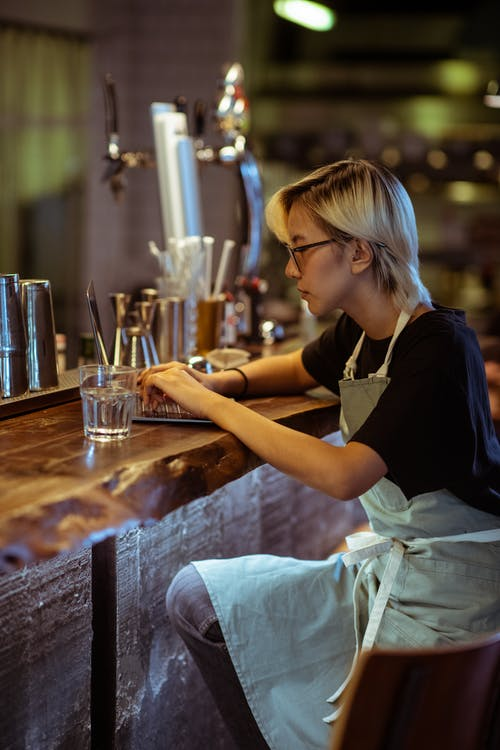 Side view of serious bartender in apron and eyeglasses using modern netbook while sitting at bar counter in modern restaurant
