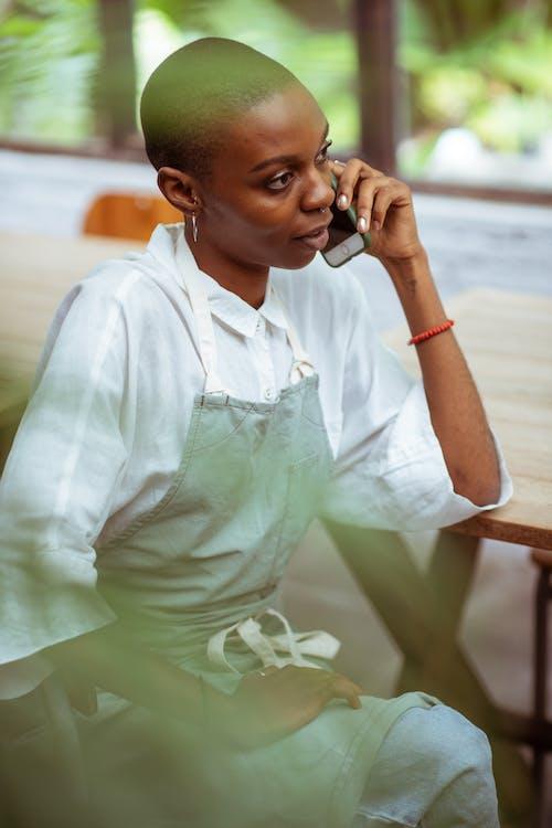 Positive black waitress talking on smartphone