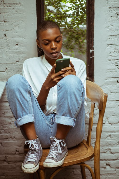 Concentrated woman in jeans chatting via smartphone