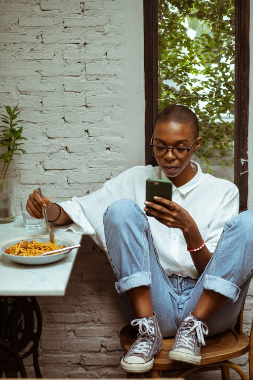 Calm thoughtful young African American lad in casual clothing sitting at table while surfing modern smartphone and eating yummy pasta against white brick wall and window