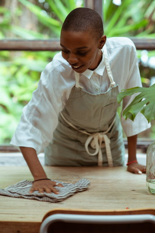 Cheerful waitress wiping wooden table against big window