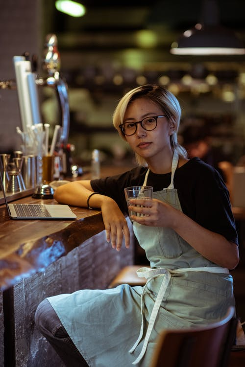 Calm waitress in apron with drink and laptop in bar
