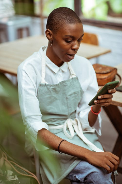 Surprised waitress in apron browsing smartphone