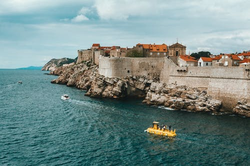 Modern boats floating on rippling sea near rocky coast of old town of Dubrovnik with historical buildings and ancient city walls